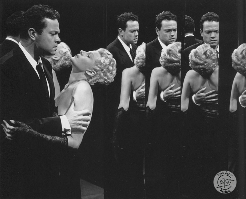 "Ned Scott's famous ""mirror"" still photograph with Orson Welles and Rita Hayworth from ""Lady From Shagnhai"". Both actors play roles which eventually intertwine in an out-of-control murder plot in Director Orson Welles' film noir crime drama, Lady From Shanghai"", 1947."
