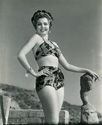 "Ann Miller models a fashionable two piece bathing suit crafted by Gantner & Mattern of San Francisco.  The venue is the outdoor studio of sculptress Cornelia Runyon who resided at the time on the cliffs overlooking the Malibu coastline in the Zuma Tract. Ann Miller worked three films in the mid-'40's for Columbia Studios, and Ned Scott photographed her often.  This photograph was taken at the time of Director Arthur Dreifus' musical comedy, ""Eadie Was a Lady"", 1945"