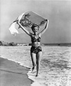 Fun loving Ann Miller, here captured while running on a Malibu Beach by Ned Scott, goes the extra mile to support her role for the Columbia Studios film, Eadie Was A Lady, 1945.  Ann plays the role of Edi Alden, a nightclub dancer who is supporting herself while attending college courses.  Director Arthur Dreifus' musical comedy, Eadie Was A Lady, 1945.  Notice the tandem surfing design on Ann's towel which billows in the wind above her head.  This scene is the beach below the cliffside residence of sculptress Cornelia Runyon.