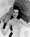 "Ann Miller frolics in the studio for Ned Scott's camera to support her role as Edithea Alden, college girl moonlighting as a nightclub dancer in Director Arthur Dreifuss' musical comedy, ""Eadie Was A Lady"", 1945.  Large hats often figure in Ned Scott's portraits of Hollywood personalities and commercial modeling subjects.  The caption on the back of this print sports the humorous quip, ""Who's looking at a hat when Ann Miller is under it?"""