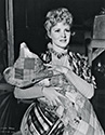 An on-set photograph of Claire Trevor, playing the outcast girl, Dallas.  This film sequence takes place at Apache Wells relay station.  The cavalry officer's wife, Mrs. Mallory, played by Loise Platt, has just given birth to a healthy baby girl not long after the stagecaoch arrived at the Apache Wells.  Dallas has just finished assisting Doc Boone, played by Thomas Mitchell, in the baby's delivery.  As she carries the newborn forward into the large room, her appearance with the bundle breaks up a viscious argument among the other stage passengers: those who wish to go back to avoid rampaging Apache warriors and those who wish to go foreward to Lordsburg.  Director John Ford's epic frontier drama, Stagecoach, 1939.