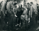 Ernie Pyle (played by Burgess Meredith) jokes with officers and men in a light moment at one of the camps at the front.  Ernie Pyle had an infectious sense of humor. Scene from Lester Cowan's authentic wartime drama 'The Story of G.I. Joe.' 1945