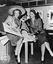 "Both of these Columbia Girls posed to support their roles in the 1944 film, Cover Girl. The studio caption reads ""...Susan Shaw and Jinx Falkenburg meet while playing themselves in Columbia Studios Rita Hayworth starrer, Cover Girl"".  Both are admiring a sketch of a new wardrobe ensemble by studio head designer, Jean Louis. Director Charles Vidor's musical comedy, ""Cover Girl, 1944."