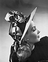 "This intriguing fashion portrait of Janet Blair highlights facial profile offset by a highly decorative hat which dominates the image.  This portrait was created at the same time Janet Blair was filming Director Alfred E. Green's ""Tars and Spars"", 1946, at Columbia Studios.  Hats were chic and popular in the day.  For a different film a year later, Columbia Studios' costume designer Jean Louis Berthault presented Rita Hayworth with a hat he had brought all the way from Paris for her costume."