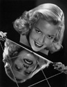 "Janis Carter photo: While Janis Carter was filming for Columbia Studios' hit adventure comedy ""A Thousand and One Nights"",1945, Ned Scott invited her to his home in La Canada for a photo session.  This compelling image is one of several to emerge from that effort.  Janis is posing above a mirrored console table for dramatic effect. Director Alfred E. Green's romantic fantasy ""A Thousand and One Nights"", 1945."