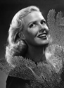 While Janis Carter was filming for Columbia Studios' hit adventure comedy 'A Thousand and One Nights'(1945), Ned Scott invited her to his home in La Canada for a photo session.  This compelling image is one of several to emerge from that effort.  Janis is holding as a prop a sprig of black coral which Ned Scott kept prominently displayed for dramatic contrast over his white brick mantel piece.