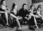 Jimmy Stewart plays failed music shop owner Jimmy Haskell, here surrounded by leggy rhumba dancers who accompany an orchestra act in Pot O' Gold, 1941.