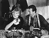 "John Wayne and Claire Trevor share a light moment on set as the Ringo Kid and the Outcast Girl in Director John Ford's epic Western saga, ""Stagecoach"", 1939."