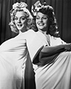 "Rita Hayworth and Leslie Brooks take five during shooting of the chorus line sequence in Director Charles Vidor's musical comedy, ""Cover Girl"", 1944.  This is an adorable off-set portrait of these two high energy stars from Columbia Studios. Leslie and Rita, a dancing duo, collaborated in several films from Columbia in the mid-'40's.   Photographs such as these were destined for newspaper publication where they stimulated public interest and improved ticket sales."