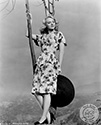 "Leslie Brooks poses outdoors on a Spring morning with appropriate pointed flower motif in the foothills surrounding Los Angeles.  Ned Scott created this image to support her role as Angela in Director Victor Saville's musical biopic of a WWII London playhouse, ""Tonight and Every Night"", 1945. During the London Blitz, this playhouse never went dark and held performances despite the nightly bombings of the city."