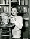 Dutch born Columbia Pictures star Nina Foch applies the finishing touches to a bust of actor Dick Dickerson in her library.  Besides starring in Columbia's film noir, My Name Is Julia Ross, Nina Foch spends her spare time creatively in this 1945 gag shot by Ned Scott.