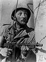 "Robert Mitchum holds his tommy gun (the Thompson machine gun) at the ready as he peers around the corner of a building in a small town in Southern Italy which is occupied by the German army.  Mitchum plays the role of Capt. Walker, respected commander of a US company which is fighting to free Italy of the occupying German forces during WWII.  Director William Wellman's authentic wartime drama, ""The Story of G.I. Joe"", 1945."
