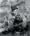 Burgess Meredith, as Ernie Pyle, enjoys a bite of C rations on the set of The Story of G.I. Joe.  Ernie often heated his rations by using gasoline.  He would dig a little hole in the dirt or sand, place some gas into the hole, cover it again with sand, and light it.  The gas would burn slowly enough for him to heat a can of food or a cup of coffee.  Ernie preferred the British COMPO rations to the U.S. Army C rations because there was more variety.  Many G.I.'s, right after landing in Oran (where Ernie came ashore during Operation Torch) would give away portions of their C rations to ragged Arab children who followed the G.I.'s around relentlessly.