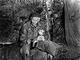 Camp dogs were everything to the combat soldier at the front.  Here Burgess Meredith plays Ernie Pyle in The Story of G.I. Joe holding the camp's mascot dog during a rainy and cold moment at the front.  Burgess Meredith was already serving in the U.S. Army on active duty as a Captain when Lester Cowan approached him to take the role of Ernie Pyle.  The Army released Meredith on an honorable discharge so he could take the role, but that occurred only after presidential adviser Harry Hopkins greased the way and George C. Marshall approved the discharge personally.