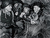 Sharing a cigarette with his Army buddies, Burgess Meredith as Ernie Pyle underscores the fact that he shared the privations of his regular soldiers while they were hunkering down in an improvised shelter, safe from enemy action, during inclement weather.