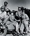 Cadet Nurse Beulah Tyler loosens up with combat veterans of the First Division on the set of The Story of G.I. Joe.  From left to right are seated Corporal Chester (Pappy)  Nowlen, Pvt. Fred Ross , Sgt. Charles Rozell, Pvt. Jim Cosso and Nurse Lt. Red Murphy.