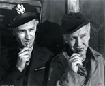 While working on the movie set, Ned Scott could always be found chewing on a match stick, an Ohio Bue Tip match stick to be precise.  And when he was not chewing on a stick, he was lighitng up and enjoying one of his Kent cigarettes.  Ernie Pyle and Burgess Meredith decided to imitate Ned Scott with synchronous poses for this photograph.  It was a light moment, one of many, and it speaks to the sense of comradery these men all felt toward one another on the set of Story of G.I. Joe.