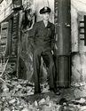 Ernie Pyle takes a break on the bombed out set of the movie Story of G. I. Joe.  Leaning against metal stack, Ernie sizes up the situation while dressed in his War Correspondent's uniform.