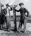 Ernie Pyle poses with Corporal James Slayton, one of the most decorated G.I.'s of World War II.  At Camp Baldwin, the headquarters for the infantry company which appeared in The Story of G.I. Joe, the track which circumnavigated the camp was renamed Pyle Road in Ernie's honor.