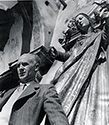 With arms outstretched , a  bas-relief statue of the Virgin Mary gathers protectively behind Ernie Pyle as he poses on the set of The Story of G.I. Joe.  Ned Scott was making a hopeful statement with this prosaic pose.  Keep Ernie Safe.  In October and November of 1944 when this photograph was taken, no one could have predicted the tragic fate which would befall Ernie has he ventured to the Pacific Theater in 1945 on non-combatant duty as a U.S. War Correspondent.