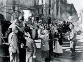 In this scene for the film Story of G.I. Joe, army cooks flanked by armed soldiers serve hot food to refugees whose homes were destroyed in a recent battle.  One of the major objectives of Director William Wellman was to convey battlefield authenticity, complete with scenes such as these which occurred in real life in Southern Italy and Northern Africa on a regular basis as the Allies advanced in their quest to oust the Germans and Italians.