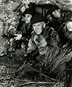Combat at the front was spartan conditions, even brutal when cold weather hit.  Burgess Meredith's character Ernie Pyle endures hardships at the front with his soldiers, from the Story of G.I. Joe.  At the front, troops took advantage of any feature of the terrain to shelter themselves both from weather and from enemy aircraft and artillery action.