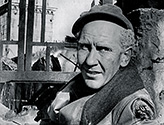 After a successful forward surge by the company at the front, Burgess Meredith as Ernie Pyle takes a moment to relax in the shelled remains of a building in a small Italian town.  Meredith is actually sitting in the back seat of a car, the only part of the car still remaining after the attack. Scene from The Story of G.I. Joe.