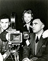 Cinematographer Russel Metty on the left, poses with associate producer David Hall and composer Ann Ronell as they flank the 35mm camera.