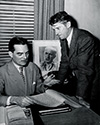 Lee Miller, seated, and Paige Cavanaugh, longtime friends of Ernie Pyle from the earlier days in news service, review and discuss the script for The Story of G.I. Joe.  Both had been hired by Lester Cowan as consultants.  They helped tune the script with Ernie Pyle.  A portrait of Ernie looms behind them as they work.