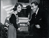 A tense moment as two characters from Fritz Lang's 'Hangmen Also Die' listen for any news broadcast about the assassination of Reich Protector Reinhold Heidrich and the resulting actions taken by occupying Nazi forces.  Actors Anna Lee and Brian Donlevy play Masha Novotny and Dr. Svoboda, both key role players in the ensuing action as the plot of this suspenseful WWII drama unfolds.