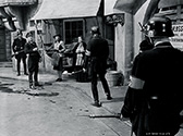 Nazi Gestapo troops scour the streets of Prague hunting for the assassin of Reich Protector Reinhard Heidrich.  Anna Lee as Masha Novotny and market proprietor Margaret Burt are transfixed with fear when Lane Bradford as the Gestapo officer directs troops in search efforts.  Fritz Lang's Hangmen Also Die, 1943