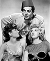 "Gene Tireney, seen here in her role as ""Poppy"" and her playful friend, Dixie, played by Phyllis Brooks are both gloated over by the supreme low-life Dr. Omar, played by Voctor Mature.  Omar has purposely currupted these two in a ploy to obstruct the plans of a wealthy Shanghai entrepreneur whose dayghter happens to be none other than the fun-loving ""Poppy"".  Director Josef von Sternberg's film noir crime drama, ""The Shanhai Gesture"", 1941."