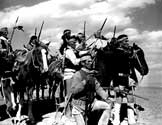 Impersonating Geronimo and his warriors, a group of local Navajo tribesman, recruited by Walter Wanger Productions for the film, gather on a bluff preparing to attach the pasengers traveling in the stagecaoch below.