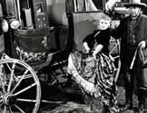 "Stagecoach movie: ""Tsk, tsk, tsk"", Buck (Andy Devine), the stage driver, says to himself as Dallas (Claire Trevor) hurls a parting insult at he women who are forcing her out of town.  ""Stagecoach"", under production by Walter Wanger and directed by John Ford, depicts the part these pioneer conveyances played in the lives of the people who rode them.  Through sun and sleet, over prairie and desert and stagecaoch carried its human cargo and as it jounced and swayed over meager trails, it brought great changes in the lives of those who rode in them.  To Dallas, the bitter outcast girl, it brought love and a new life."
