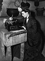 Louise Platt in costume on the set of Stagecoach takes a moment to type a letter between scenes