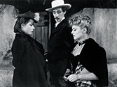 Stagecaoch 1939 film: Claire Trevor, as outcast girl Dallas, gets a sneer from the cavalry officer's wife, Lucy Mallory, played by Louise Platt and the Southern gentleman and arrogant gambler, Hatfield, played by John Carradine.