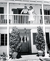 Gene Autry and his wife smile a greeting from the balcony of their home in San Fernando Valley.  This photograph supported Columbia's film 'The Strawberry Roan', 1948.