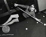 Evelyn Keyes lines up a challenging shot on the pool table at her home.  This image was used to support her role in Johnny O'Clock, 1948